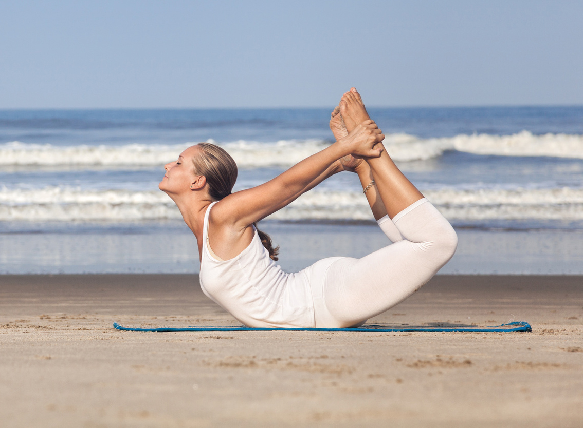 Yoga dhanurasana bow pose by woman in white costume on the beach near the ocean in Goa, India